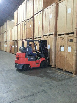 Storage warehouse worker moving containers with forklift