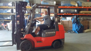 Storage worker driving forklift